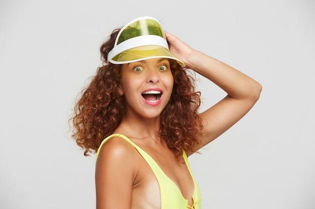 젊은 green-eyed 빨간 머리 여성 유지의 실내 사진은 흰색 배경 위에 서서 카메라를 놀랍게 보면서 그녀의 머리에 손을 들고