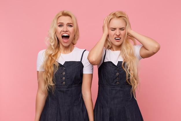 彼女の妹がピンクの背景で隔離され、大声で叫んでいる間、彼女の目を閉じて、上げられた手で耳を覆っている若い長い髪の金髪のきれいな女性の屋内写真