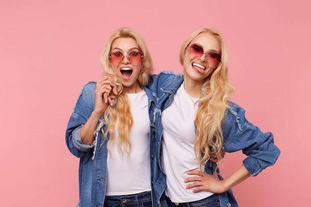 カジュアルな服装でピンクの背景の上に立って、笑いながら楽しんでいる間、波状の髪型で若い素敵な金髪の双子の屋内写真