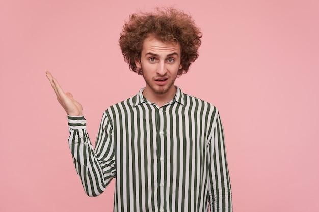 불쾌한 얼굴로 카메라를보고 혼란스럽게 손바닥을 올리는 젊은 꽤 곱슬 빨간 머리 남성의 실내 사진, 캐주얼 옷에 분홍색 벽 위에 포즈