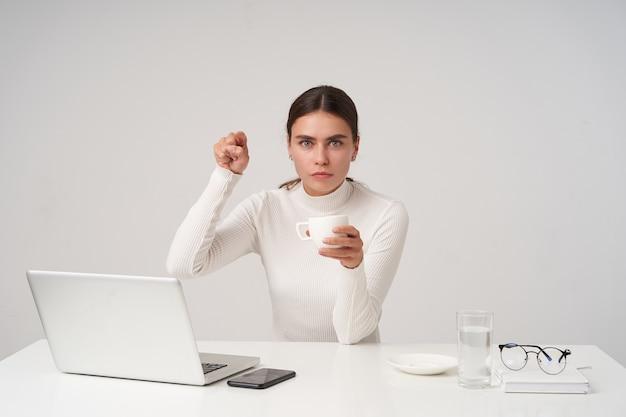 Фотография в помещении молодой довольно темноволосой дамы с прической, указывающей на поднятый указательный палец и серьезно смотрящей, позируя над белой стеной