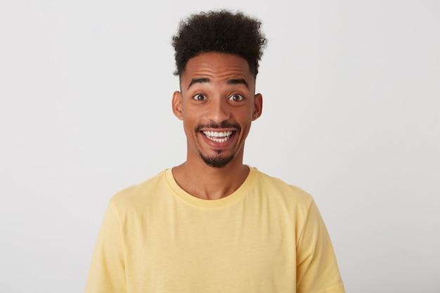 짧은 곱슬 머리를 가진 젊은 꽤 어두운 피부의 면도하지 않은 남자의 실내 사진