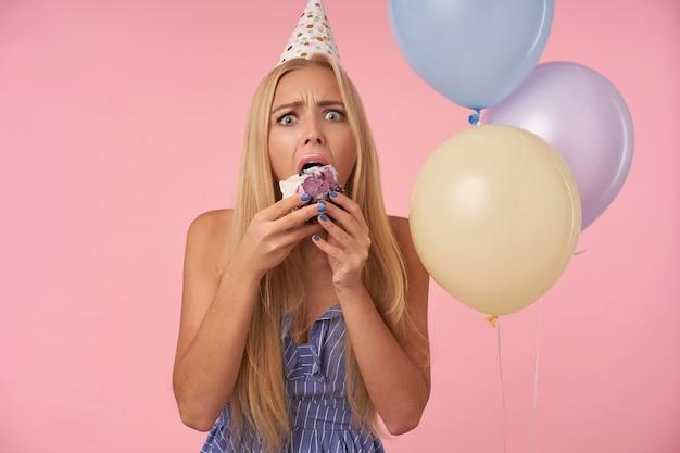 파란 여름 드레스와 생일 모자를 쓰고 긴 금발 머리를 가진 젊은 예쁜 여성의 실내 사진, 케이크를 먹고 넓은 눈으로 카메라를 보면서 놀란다.