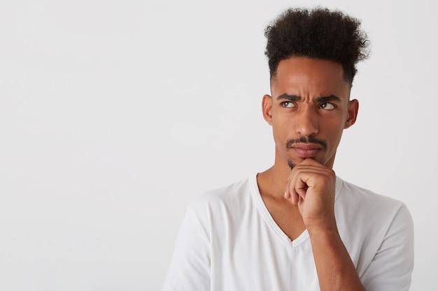 젊은 의아해 어두운 피부 면도되지 않은 곱슬 남자의 실내 사진은 뭔가에 대해 우려하고