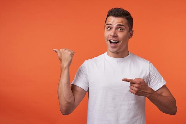 オレンジ色の背景の上に立って、上げられた手で脇を指してカメラを感情的に見ている若い短い髪のブルネットの男性の屋内写真
