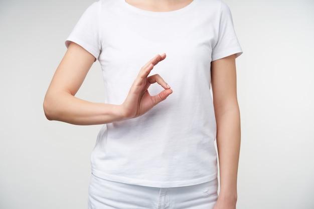 白い背景の上に立っている間彼女の指でokジェスチャーを形成するカジュアルな服を着た若い女性の屋内写真。手話の概念
