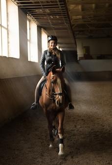 Фотография в помещении молодой женщины-жокея верхом на лошади на манеже