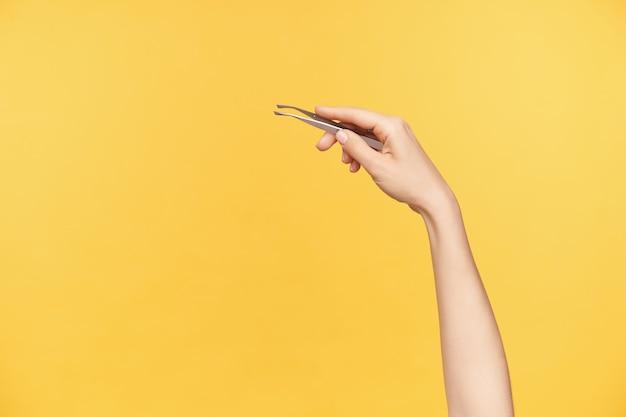 若い女性の手をピンセットを入れたまま持ち上げ、オレンジ色の背景の上に隔離された状態で眉毛をツイーズする屋内写真。美容とフェイスケアのコンセプト