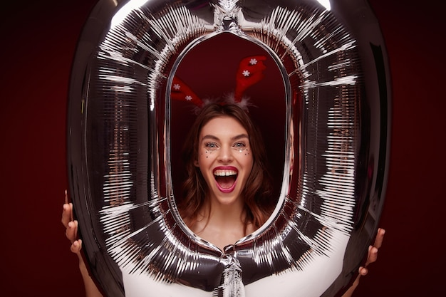 Indoor photo of overjoyed young brown haired female wearing festive makeup while posing over big air balloon, rejoicing nice new year party together with friends, isolated