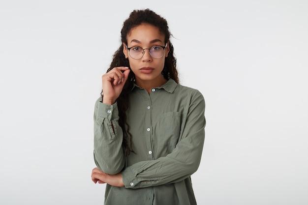 Foto interna di pensieroso riccio bruna dalla pelle scura donna con gli occhiali alzando la mano al viso mentre guarda seriamente la fotocamera, isolato su sfondo bianco