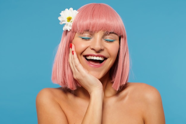 Indoor photo of pleasant looking happy young female with short pink hair keeping her eyes closed while leaning her head on raised hand, smiling cherfully over blue background