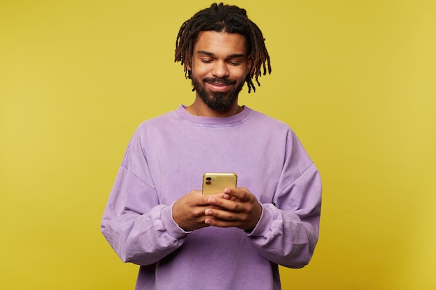 Indoor photo of pleased young dark skinned brunette male keeping smartphone in raised hands and looking positively on screen, isolated over yellow background