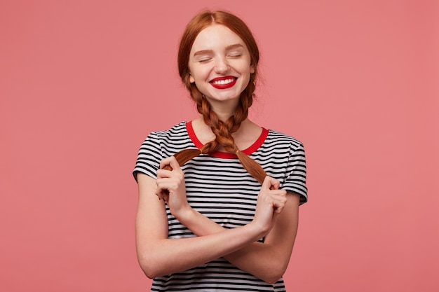 Indoor photo of pretty red-haired girl with red lips playing with two braids in hands dressed in stripped t-shirt, dreams imagines happy moments with closed eyes isolated