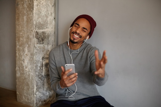 Indoor photo of pretty young bearded dark skinned man posing over white wall and enjoying music track, raising palm emotionally while singing with closed eyes