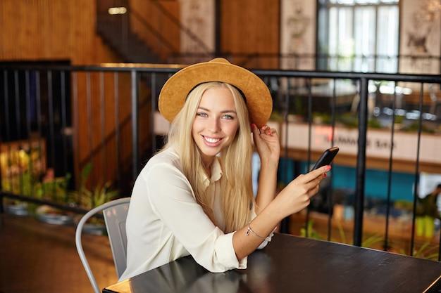 Foto interna di bella giovane donna bionda dai capelli lunghi seduto al tavolo sopra il ristorante durante la pausa pranzo, guardando allegramente con il cellulare in mano