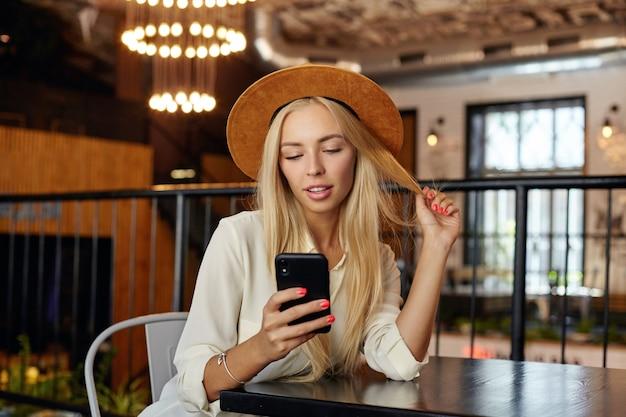 Foto interna di bella giovane donna bionda dai capelli lunghi seduto al tavolo sopra l'interno del bar, tenendo lo smartphone in mano e guardando lo schermo con un sorriso morbido
