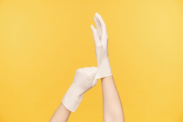 Indoor photo of raised female's hands taking on white rubber gloves while preparing for cleaning house, posing over orange background. human hands concept