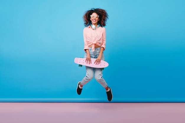 Indoor photo of relaxed african woman in cotton pink shirt dancing with longboard. portrait of jumping curly girl with brown skin enjoying with skateboard in summer.