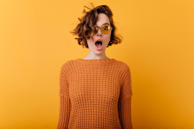 Indoor photo of romantic shocked woman in trendy sunglasses standing near yellow wall