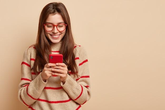 Foto interna di testi di adolescenti soddisfatti su cellulare, legge articoli interessanti online, indossa abiti casual, crea una nuova pubblicazione sulla propria pagina web, isolata su un muro marrone con spazio libero