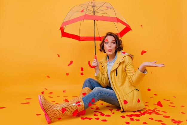 Indoor photo of spectacular girl wears rubber shoes and blue denim pants posing with umbrella. portrait of joyful lady sitting on the floor with red paper hearts.