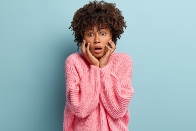 La foto dell'interno della donna dalla pelle scura emotiva sorpresa tiene la bocca aperta, tocca le guance, esprime grande incredulità, stupita dalle ultime notizie, isolata sopra il muro blu. espressioni facciali