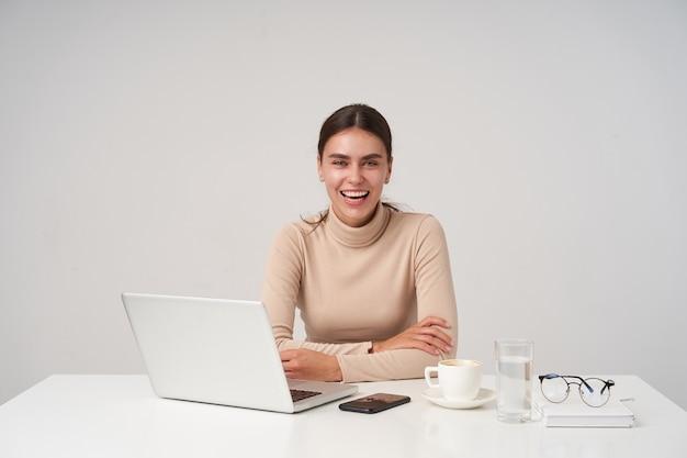 Foto interna di giovane donna dai capelli scura allegra con trucco naturale che piega le mani sul piano di lavoro e ride felicemente mentre guarda la fotocamera, isolata sopra il muro bianco