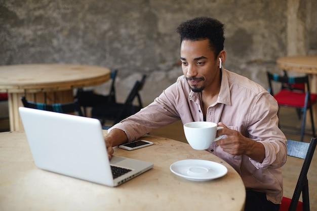 Foto al coperto di giovane maschio dalla pelle scura con la barba che lavora fuori ufficio, seduto a tavola su uno spazio di coworking e controlla la posta sul suo laptop, tenendo la tazza di caffè in mano alzata