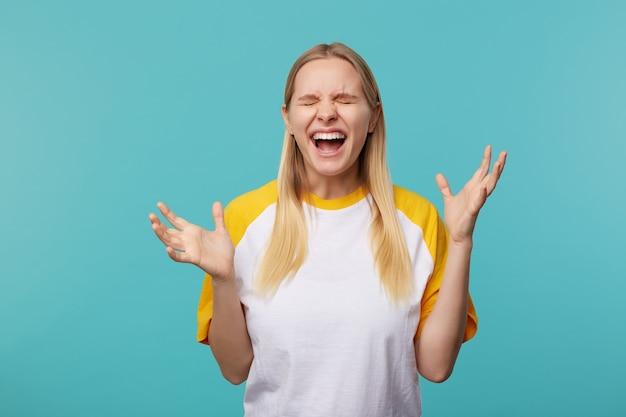 Foto interna della giovane donna bionda dai capelli lunghi eccitata aggrottando le sopracciglia il viso con gli occhi chiusi e sollevando emotivamente le sue mani, isolate su sfondo blu