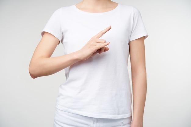Foto dell'interno di giovane donna dalla carnagione chiara vestita in abiti casual che parlano la lingua dei segni e che mostrano l'aereo con la mano alzata, isolata sopra priorità bassa bianca