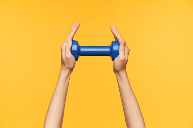 Indoor photo of young fair-skinned lady's hands being raised while keeping blue dumbbell in it, visiting fitness class and exercising arms, isolated over yellow background