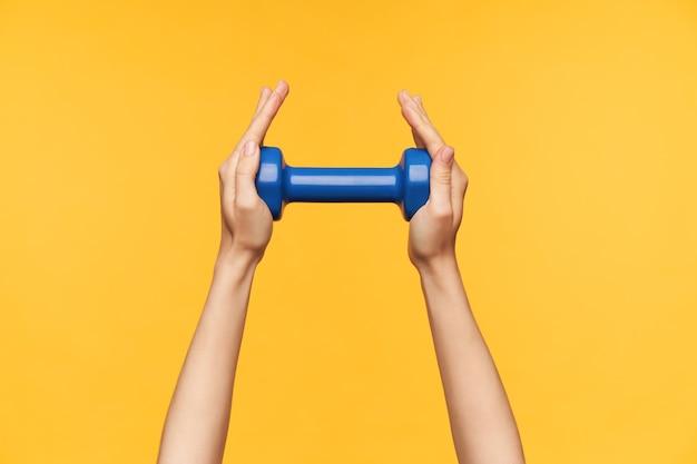Foto al coperto delle mani della giovane donna dalla pelle chiara che vengono sollevate mantenendo il manubrio blu, visitando la lezione di fitness e esercitando le braccia, isolato su sfondo giallo