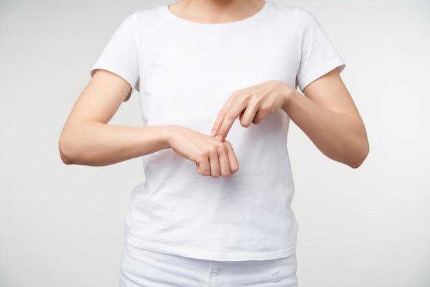 Foto interna di una giovane donna che utilizza il linguaggio dei segni per mostrare il poliziotto, vestito con abiti casual mentre si trova su sfondo bianco. mani umane e concetto gesticolare