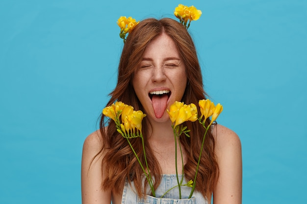 Indoor photo of young good looking foxy woman with curls keeping her eyes closed and sticking out her tongue while posing over blue background with yellow flowers