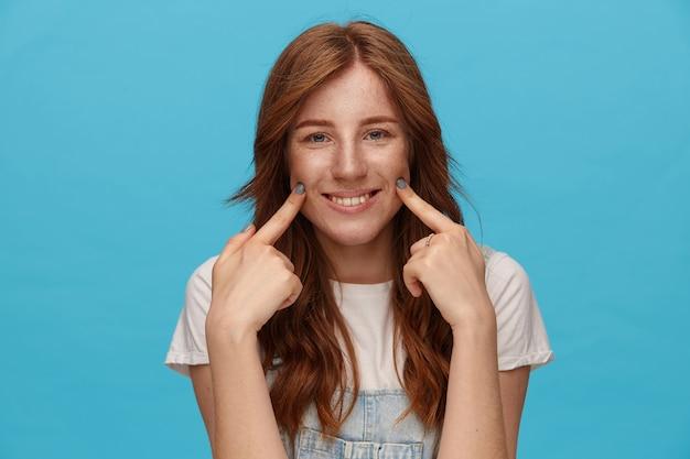 Foto interna della giovane signora dai capelli verdi dagli occhi verdi che tiene gli indici sollevati sulle guance e guarda felicemente la fotocamera con un ampio sorriso, in piedi su sfondo blu