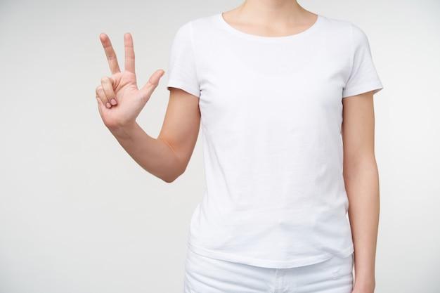 Foto interna di giovane donna in abiti casual che mostra tre dita durante il conteggio, in piedi su sfondo bianco. mani umane e concetto gesticolare