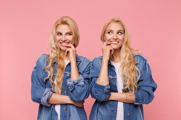Foto interna di giovani donne bionde dai capelli lunghi che guardano volentieri da parte con un ampio sorriso e mantenendo gli indici sulle labbra, isolate su sfondo rosa
