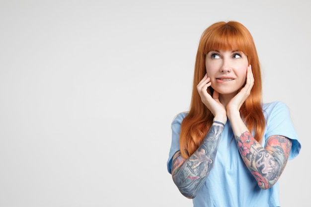 Indoor photo of young long haired redhead lady with casual hairstyle holding raised hands on her face and biting worringly lips while looking aside, standing over white background