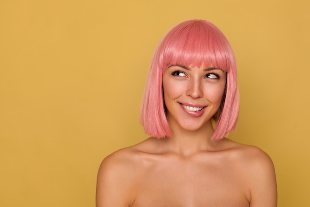Indoor photo of young lovely blue-eyed woman with short pink hair looking thoughtfully upwards and biting underlip with light smile, standing against mustard wall