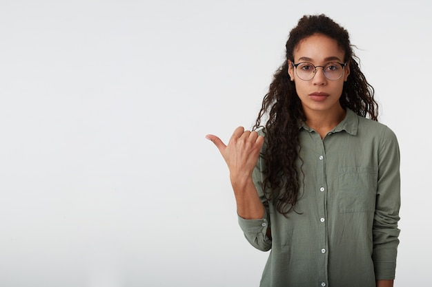 Foto interna di giovane bella bruna riccia dalla pelle scura donna che punta con il pollice da parte mentre guarda la fotocamera con le labbra piegate, in piedi su sfondo bianco