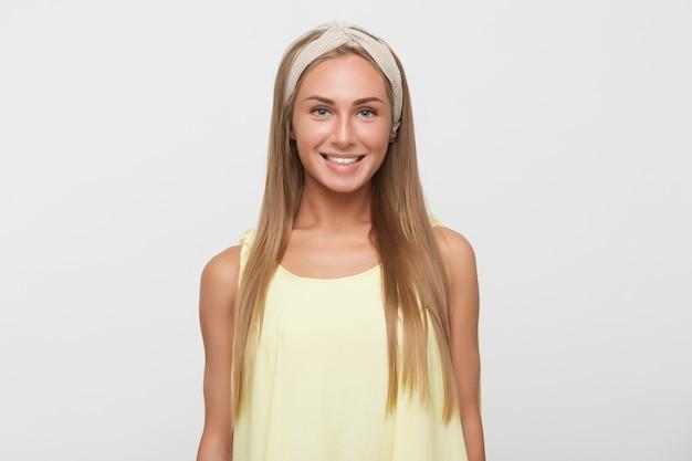 Foto interna di giovane bella donna felice con lunghi capelli biondi che mostra le sue piacevoli emozioni mentre posa su sfondo bianco, mantenendo le mani lungo il corpo