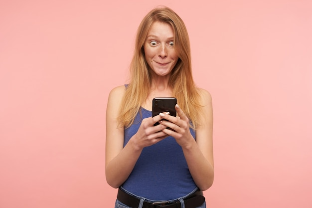 Indoor photo of young lovely redhead woman with casual hairstyle keeping mobile phone in raised hands and being surprised while reading message, isolated over pink background