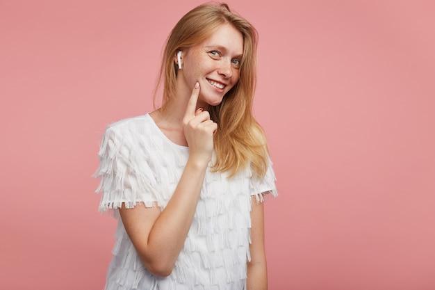 Foto interna di giovane donna adorabile con capelli foxy mantenendo l'indice sulla guancia mentre guarda allegramente la fotocamera con un ampio sorriso, in posa su sfondo rosa