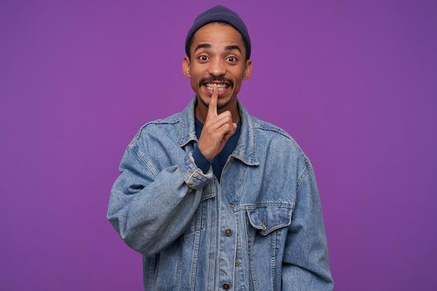 Foto interna del giovane maschio brunetta piuttosto barbuto che tiene l'indice sulle labbra mentre guarda, chiamando per mantenere il segreto, in piedi sopra il muro viola