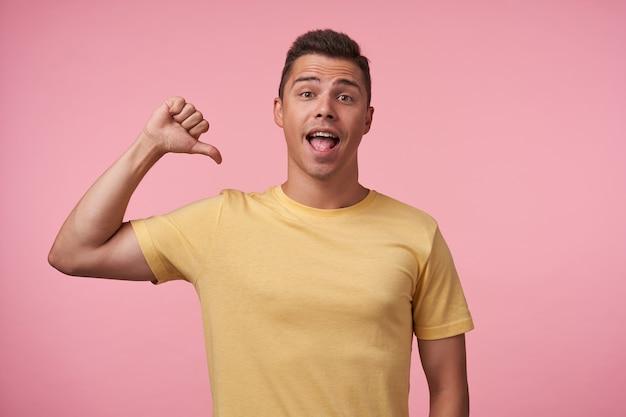 Foto interna del giovane ragazzo dai capelli castani con taglio di capelli corto che sfoglia su se stesso mentre guarda eccitatamente la fotocamera con la bocca aperta, in posa su sfondo rosa