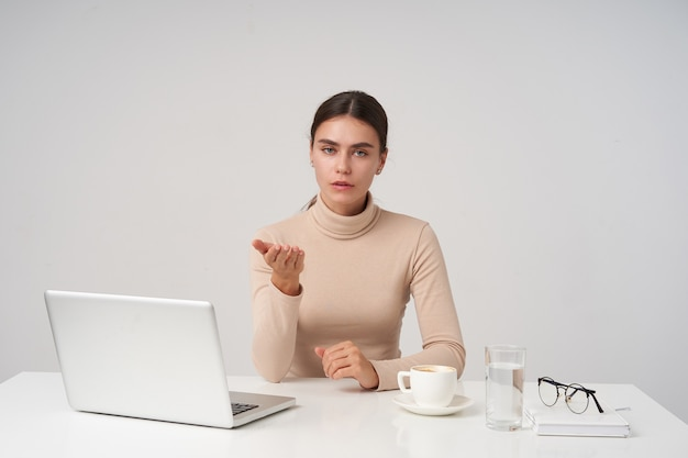 Indoor photo of young pretty dark haired lady dressed in beige poloneck sitting at table with laptop and cup of coffee, raising perplexedly palm while looking at camera with puzzled face