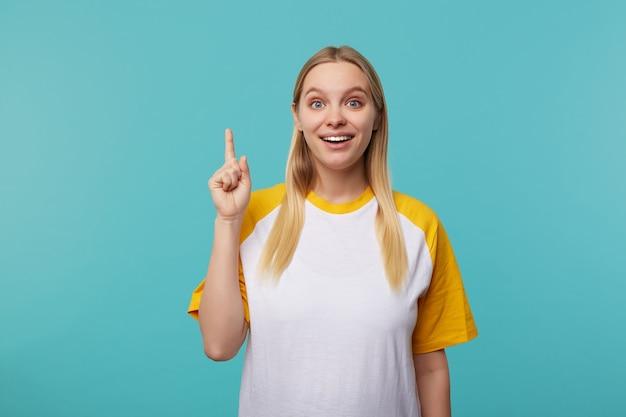 Foto interna di giovane donna piuttosto bionda vestita in abbigliamento casual alzando la mano con segno idea mentre guarda con entusiasmo la fotocamera, posa su sfondo blu