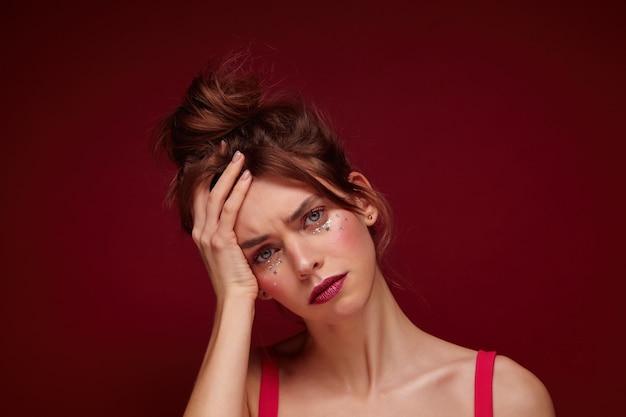 Foto dell'interno di giovane femmina abbastanza mora triste con trucco da sera che si appoggia la testa sul palmo sollevato e guarda tristemente, in posa