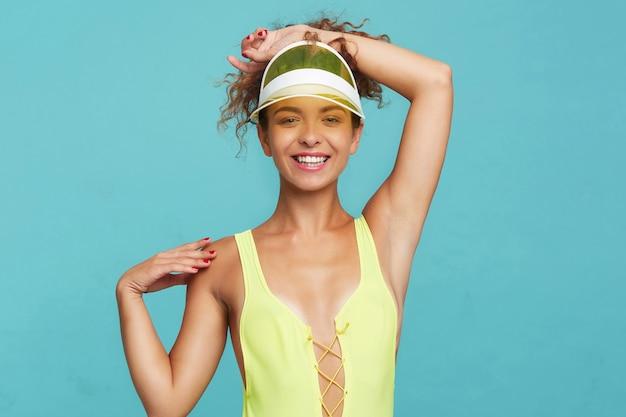Foto interna di giovane donna sottile piuttosto riccia con trucco naturale che guarda l'obbiettivo con un sorriso affascinante e tenendo le mani alzate, isolato su sfondo blu