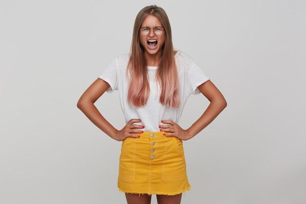 Foto interna di giovane donna bionda dai capelli lunghi stressata che aggrotta le sopracciglia mentre grida ad alta voce, tenendosi per mano sulla sua vita mentre si trova sopra il muro bianco